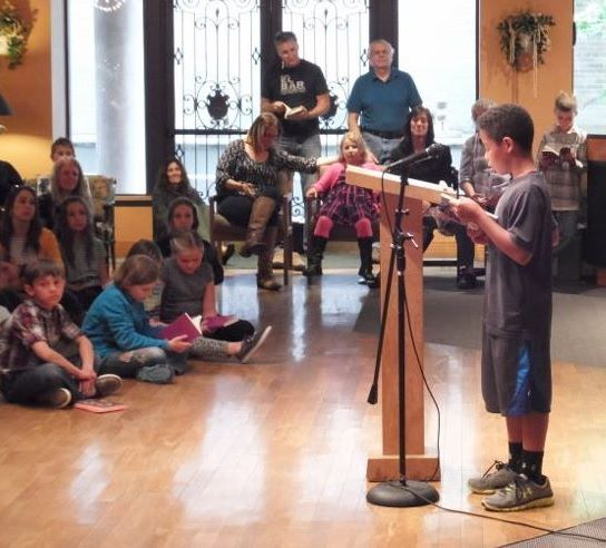 A young writer reads from his work after participating in a summer writing camp at The Cabin.